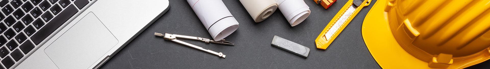 Laptop, kask, cyrkiel, arkusze papieru, nóż introligatorski